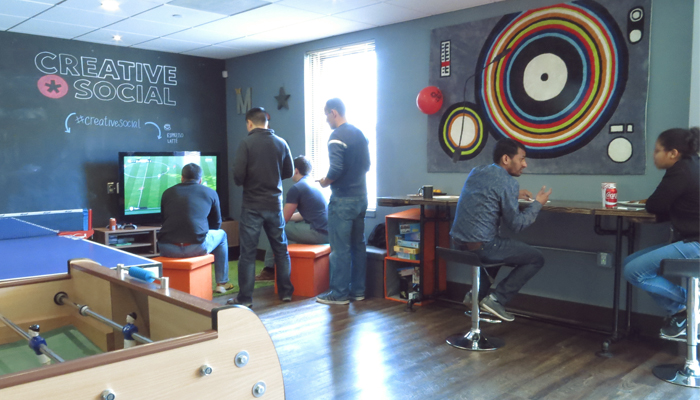 Employees hanging out in the Breakroom with ping pong table, foosball, and tv.